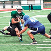 Special photo by John Hasler<br /> Muskogee quarterback Mikey Rodriguez, left, tries to avoid the tackle of Checotah's Dylan Mills during Wednesday's action at the Muskogee team camp on Creek Nation Field at Indian Bowl.