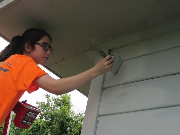 Bella Magallon of Muskogee First Assembly of God paints under an eave Monday. Bella is joining scores of teens for Mission Muskogee.