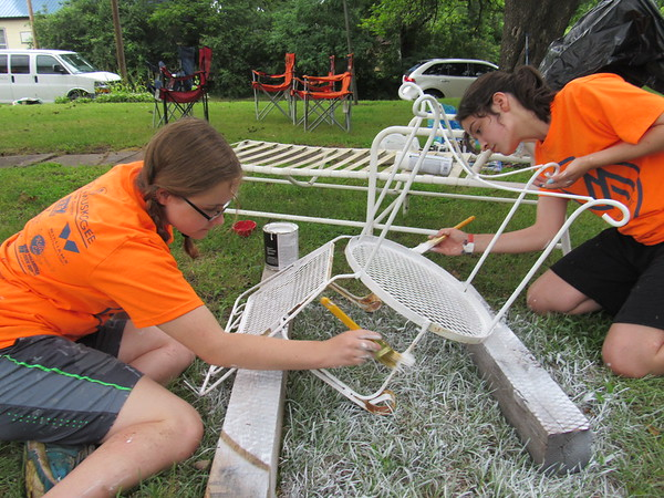 First Baptist Church youth Hanna Cariker, left, and Libby Jones apply rust-proof paint on a lawn chair during Mission Muskogee.
