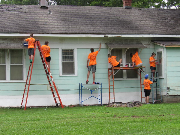 CATHY SPAULDING/Muskogee Phoenix<br /> First Baptist Church youth go to various heights to paint a house during Monday morning rain. They were among several youth groups participating in Mission Muskogee.