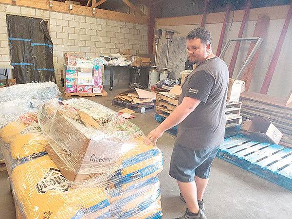 CHESLEY OXENDINE/Muskogee Phoenix<br /> Volunteer Ryan Ramsey gives a tour of the back room at a donation center housed in a 1311 N. Main St., warehouse.