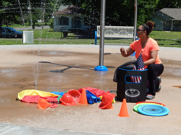 Staff photo by Mark Hughes<br /> Denise Hickman, Muskogee parks' recreation program manager, is caught in a sudden shower when a child activated the splash pad at Beckham Park while Hickman was checking out her game equipment for Saturday's P.E. in the Park. Hickman said it didn't matter, as all of her equipment is waterproof.