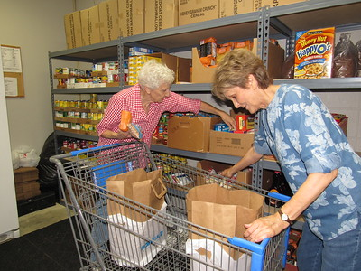 CATHY SPAULDING/ Muskogee Phoenix Volunteers Betty Mauldin, left, and Marcheta Lashley fill a client's grocery bags at Muskogee Community Food Pantry.