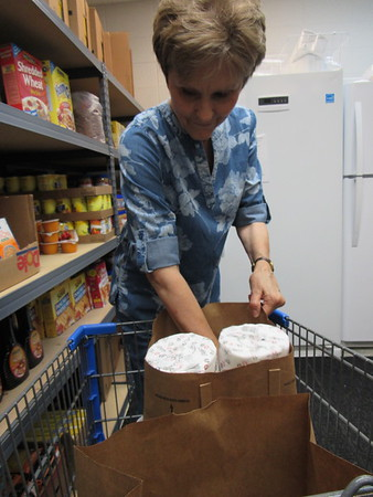 CATHY SPAULDING/ Muskogee Phoenix<br /> Muskogee Community Food Pantry volunteer Marcheta Lashley fills grocery bags with toilet paper and canned goods.