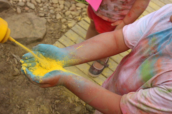 Staff photo by Harrison Grimwood<br /> A boy at the learning center collects yellow powder to share with his friends.