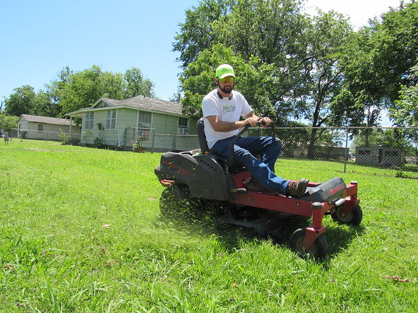 Staff photo by Cathy Spaulding<br /> Kenneth Claypool mows a lawn during a break. Claypool offers lawns services during his off-time as a water technician with the City of Muskogee.