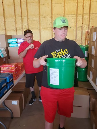CHESLEY OXENDINE/Muskogee Phoenix <br /> Church of Christ member Carlos Davila directs volunteer Thomas Holton during a tour of the Church of Christ's resource center at 806 Lee St. The center has food, water, clothes and cleaning supplies for those affected by the floods.