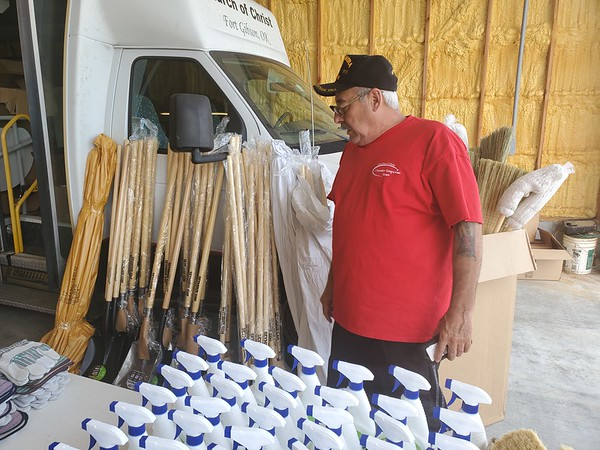 CHESLEY OXENDINE/Muskogee Phoenix<br /> Church of Christ member Carlos Davila discusses the cleaning supplies available at the Fort Gibson church for flood survivors.