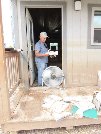CATHY SPAULDING/Muskogee Phoenix<br /> Stan Sheffield of S&J Farms inspects farm records he's trying to dry. The farm office, plus hundreds of acres of wheat and corn, were damaged in area floods.