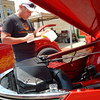 Staff photo by Mark Hughes<br /> Mel Post makes notes after inspecting an engine during Fort Gibson's annual Car, Truck and Motorcycle Show on Saturday. When judging, Post said, every vehicle starts out with 50 points, and he deducts for imperfections.