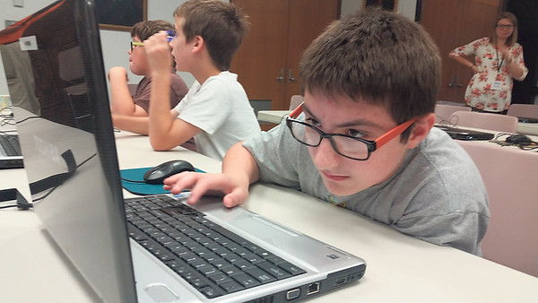 Staff photo by Cathy Spaulding<br /> Nathan Stanke, 11, concentrates on where to move his cursor during a video game coding session at Muskogee Public Library.
