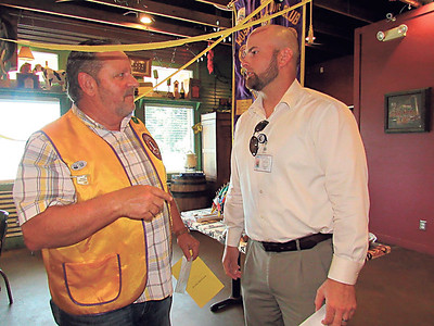 KENTON BROOKS/MuskogeePhoenix Rick Riggs, left, president of the Muskogee Noon Lions Club, talks with Dennis Read, business manger at Oklahoma School for the Blind, at the club's annual Benevolent Donor Banquet on Wednesday. The school received a check for $500 from the Lions Club.