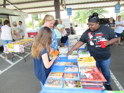 CATHY SPAULDING/Muskogee Phoenix Ben Franklin STEM Academy Librarian Kim Davison, right, helps 11-year-old Sierra Van Gordon and her mother, Ara Van Gordon select books during a recent book giveaway sponsored by Muskogee Public Schools librarians. STEM stands for Science Technology Engineering Math.