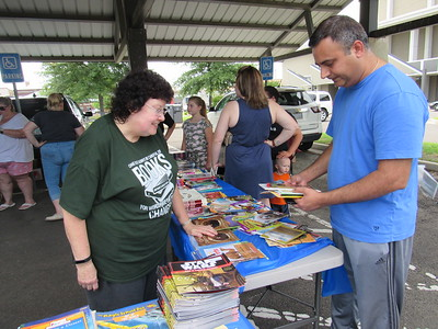 CATHY SPAULDING/Muskogee Phoenix Creek Elementary School Librarian Cathy Anthis helps Dhaval Gandhi select books during a recent book giveaway. Gandhi said his 8-year-old son is an avid reader during the summer.