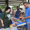 CATHY SPAULDING/Muskogee Phoenix<br /> Creek Elementary School Librarian Cathy Anthis helps Dhaval Gandhi select books during a recent book giveaway. Gandhi said his 8-year-old son is an avid reader during the summer.