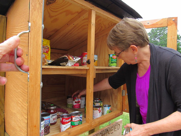 Staff photo by Cathy Spaulding<br /> The Rev. Dawn Richards of First United Methodist Fort Gibson arranges canned goods inside a Blessing Box. Fort Gibson bus driver Jason McLaughlin built the box as a way to help people in need and to enable people to help those in need.