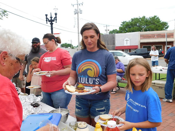 KENTON BROOKS/Muskogee Phoenix Shaun Norris, right, stands with family members Stephanie Norton, Shannon Norris and Bostynne Norton to pick up hamburgers during Saturday's Fort Gibson Community Party. Pam Martin served them the food. The free event was for people to take a break from cleaning up after the flood affected the town.