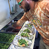 Special photo by Travis Sloat<br /> Corey McTavish, a food service vendor from Not'Cho Ordinary Taco, prepares a row of Hawaiian Surf and Turf tacos for customers at G Fest on Friday afternoon. The taco stand is one of several vendors who returned for the second music festival.