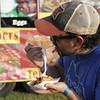 Staff photo by Harrison Grimwood<br /> Joey Ramos of Texas takes a delightful bite of bacon mac and cheese fries, one of the oddities of the festival.