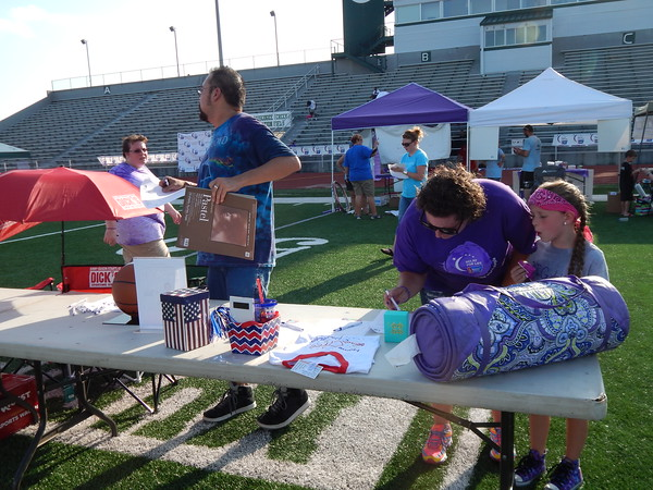 Staff photo by Cathy Spaulding<br /> Louis Hogner, left, picks up a silent auction bid sheet while Tiffany McCoin and Kendrie McCoin, 6, bid on a silent auction item Friday at the Relay for Life. The relay, held at Indian Bowl, raised money for the American Cancer Society.
