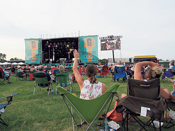 Staff photo by Cathy Spaulding<br /> Fans wave as the Swon Brothers perform on the main stage Saturday at G Fest. Zach Swon, on the screen, encouraged fans to wave to cool things off.