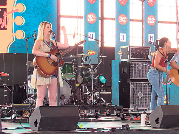 """Staff photo by Cathy Spaulding<br /> Madi Metcalf, left, and Alaska Rayne Holloway of the Tulsa group Alaska and Madi sing """"Go back to your trailer"""" on the G Fest OKPOP Stage. The stage, located in a former airplane hangar, was one of four G Fest venues."""