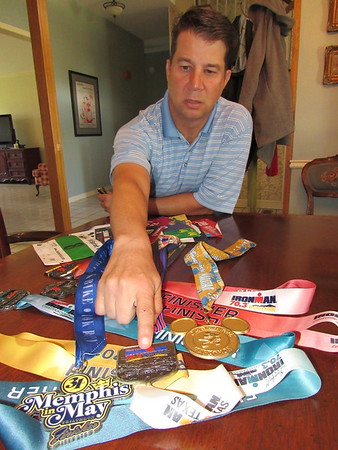 Staff photo by Cathy Spaulding<br /> Jon Kolb shows some of the medals he earned for competing in triathlons, including the grueling Ironman Triathlons.