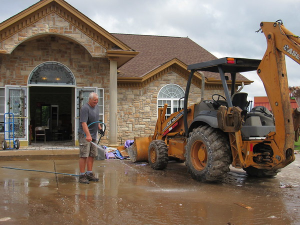 CATHY SPAULDING/Muskogee Phoenix<br /> James Fast hoses down a front end loader while other volunteers clear flood-damaged walls from the eye clinic of Dr. Debbie Coy, O.D. Fast was one of several volunteers who helped clean the building over the past few weeks.