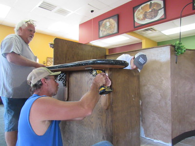 Derek Pfeifer, left, watches Randy Guthrie drill a counter into place at Fajita Rita's restaurant while Chandler Wing works on the other side. The three are helping owners get the restaurant ready to open this week.