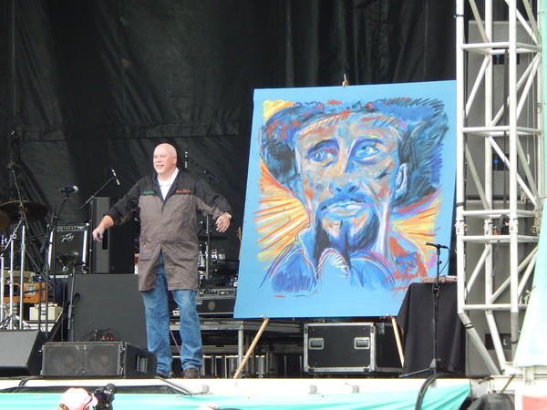 Staff photo by Mark Hughes<br /> Richard Hight acknowledges the crowd's applause after completing an oversized portrait of Merle Haggard on Saturday afternoon at G Fest. The drawing will be given to the Oklahoma Music Hall of Fame.