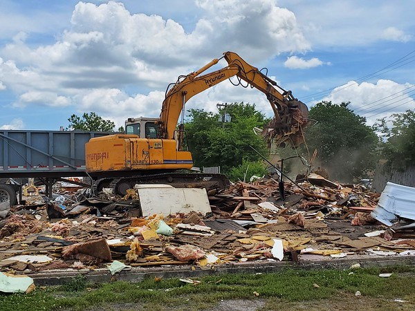 CHESLEY OXENDINE/Muskogee Phoenix<br /> Jake Capps with Madewell Ultimate Construction cleans up debris left after the demolition of an old Sheets gas station on East Okmulgee Avenue.
