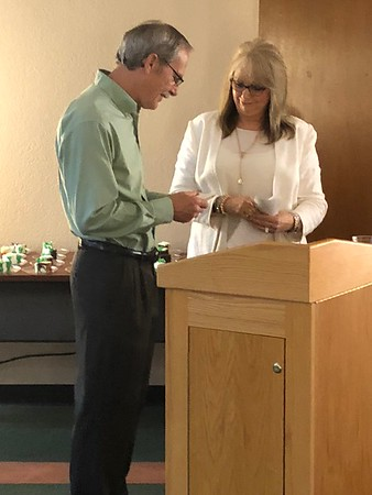 CHESLEY OXENDINE/Special to the Phoenix<br /> Outgoing Muskogee Public Schools Superintendent Mike Garde (left) receives a retirement gift — vacation money — from Board of Education Secretary Carla Cooper.