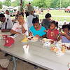 Staff photo by Cathy Spaulding<br /> Ahriyana Walker left, enjoys barbecue while Zalhiya Walker, center, and Deztynni Walker work on sticking straws in their drinks at Muskogee's Juneteenth celebration, held Monday at Elliott Park. Muskogee Juneteenth celebration organizer Wilma Newton said about 700 people attended Monday's celebration. The celebration included a feast featuring corn on the cob and barbecue, inflatable bounce houses and booths. Juneteenth commemorates the end of slavery in the United States. According to the America's Library.gov website, the day marks June 19, 1885, when Union Soldiers arrived in Texas to spread the word about the Emancipation Proclamation, freeing slaves. The news reached Texas more than two years after the proclamation was issued, and two months after the Civil War ended.