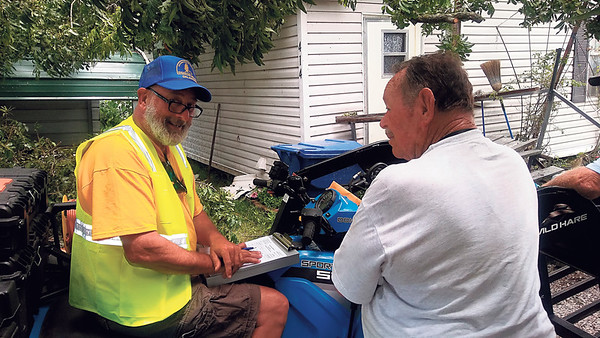 Staff photo by Wendy Burton<br /> Southern Baptist Convention Disaster Relief Volunteer Murphy Murphy, left, talks with Webbers Falls resident Bob Wampler about damage Wampler's home suffered in Saturday's storm. Wampler, whose home was one of two destroyed by trees falling in Webbers Falls, said he was blown back into his house by the storm when he tried to go outside to get in a storm shelter.