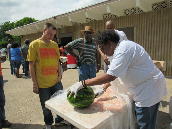 CATHY SPAULDING/Muskogee Phoenix<br /> Shelia Crutcher slices watermelon to serve to Joseph Palmore, left, and Sylvester Ousley, second from left, during Tuesday's Juneteenth celebration.