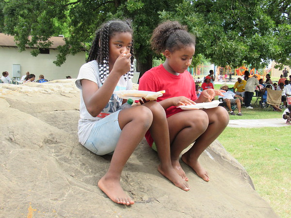 CATHY SPAULDING/Muskogee Phoenix<br /> Terrah Williams, left, and Damari Hollis, both 10, dine while seated on one of Elliott Park's huge boulders during Tuesday's Juneteenth celebration.