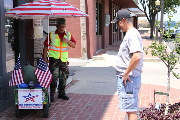"Staff photo by Harrison Grimwood<br /> ""The Walking Veteran,"" Thomas Wayne Hudson, left, chats with Glenn Stewart of Owasso as he passes through Muskogee. Hudson is walking from Las Vegas to Washington to bring attention to ""the abuses that veterans endure,"" according to his website,  <a href=""http://www.walkingveteran.com"">http://www.walkingveteran.com</a>. While in Muskogee, he visited the regional office of the Department of Veterans Affairs on behalf of a disabled veteran, hoping to help her get benefits for service-related injuries. Hudson's website says his journey will conclude with a rally in Washington on Veterans Day."