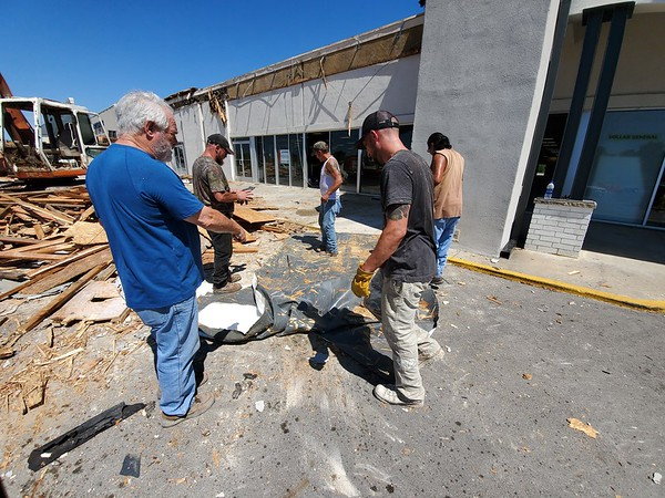 CHESLEY OXENDINE/Muskogee Phoenix<br /> Larry Henley (left) and Chris Velona (right) are joined by other Henley Construction employees while cleaning away the facade of the former Hastings Entertainment at Shawnee Crossing on Thursday morning.
