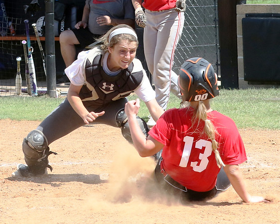 Phoenix special photo by John Hasler<br /> Red's Kylee Jo Sparks slides under the tag of White's Madison Pratt in the championship game of the Heartland Classic in Warner.