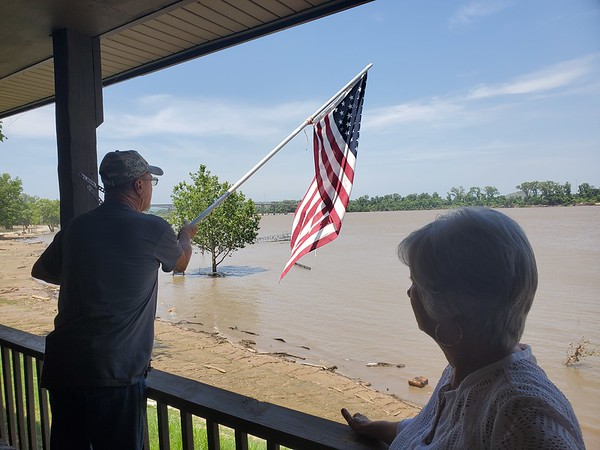 Webbers Fall Mayor Sandy Wright (right) watches as her husband James Wright fixes a flagpole on their back porch overlooking a swollen Arkansas River.