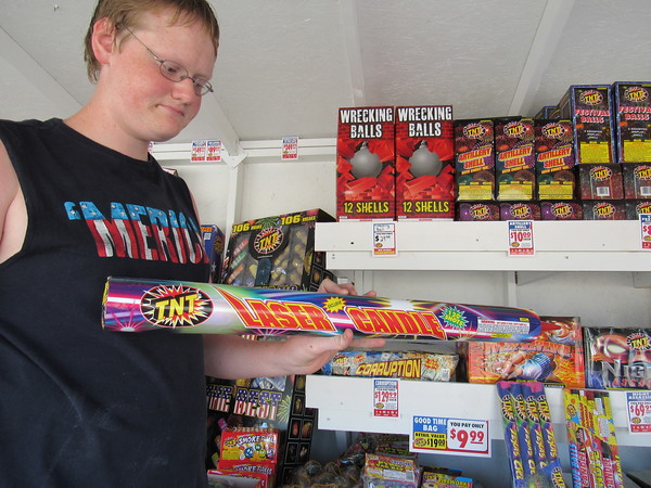 Staff photo by Cathy Spaulding<br /> Andrew Wilson, 17, shows a Roman candle capable of firing 120 shots. A variety of fireworks are available at 32nd Street and Okmulgee Avenue. The sale benefits Freedom Fellowship Nazarene. Fireworks are also being sold throughout Muskogee and other area communities.