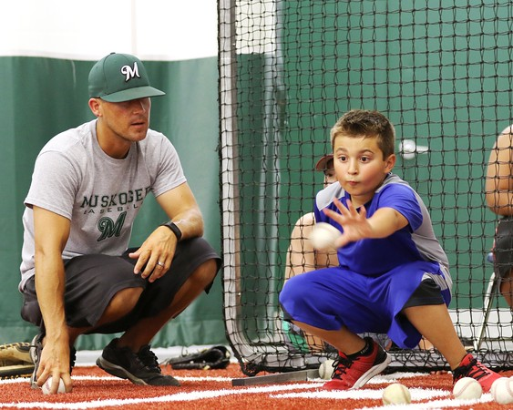 Phoenix special photo by John Hasler<br /> Muskogee High baseball coach Nathan Frisby does catcher training with Bucky Kelly, 9, during the Rougher Baseball Academy session on Wednesday at Muskogee High School.