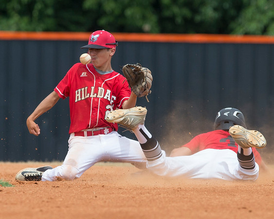 VON CASTOR/Phoenix special photo<br /> Hilldale's Landon Evans waits on a ball as Red's Connor Bastarache slides into second base Friday afternoon in the first round of the Heartland Classic at Connors State in Warner.