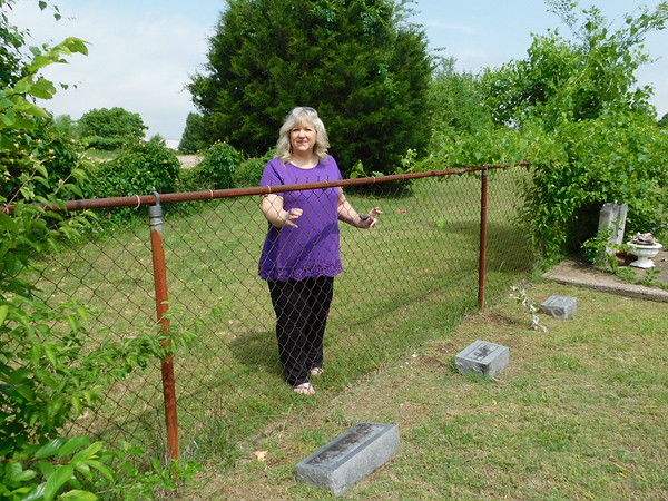 KENTON BROOKS/Muskogee Phoenix<br /> Becky Parkinson, treasurer of the Frozen Rock Cemetery, stands at the fence where some of her relatives are buried.