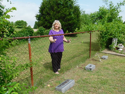 KENTON BROOKS/Muskogee Phoenix Becky Parkinson, treasurer of the Frozen Rock Cemetery, stands at the fence where some of her relatives are buried.