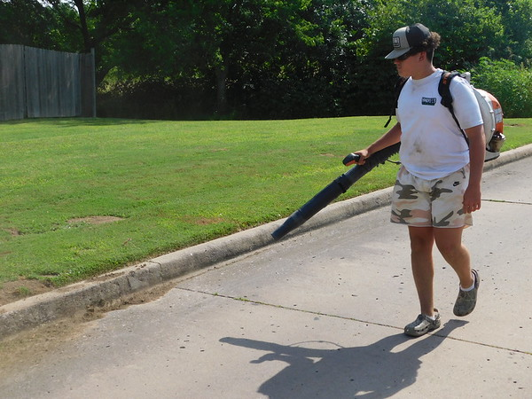 AUSTIN HEADLEE/Muskogee Phoenix<br /> Bryton McPherson, Yandell's Turf Care landscaper, blows leaves and debris after finishing a client's lawn. McPherson has worked with Yandell's for two years.