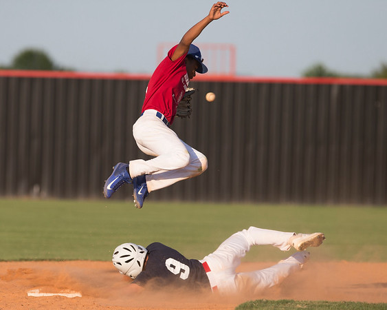 Phoenix special photo by Von Castor<br /> Crimson's Jakoby Gouldsby jumps to catch a  throw as Navy's Gatlin Goodson slides into second base Saturday in the Heartland Classic at Hilldale.