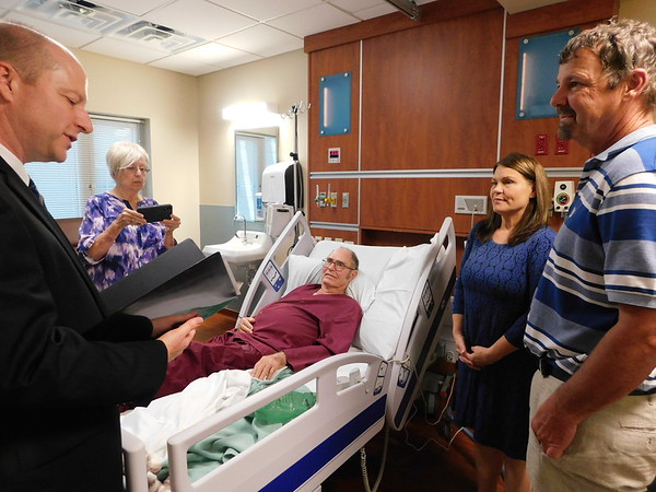 KENTON BROOKS/Muskogee Phoenix<br /> Cynthia Strader, second from right, and Daniel Holder get married Monday in her father Charles' room at the Jack C. Montgomery VA Medical Center. Charles Strader has been diagnosed with terminal leukemia, and Cynthia wanted her father to be at the wedding. The Rev. Joel Allen McBroom officiates at the wedding while Charles Strader's wife Judy records the ceremony. Charles and Judy have been married for 50 years.