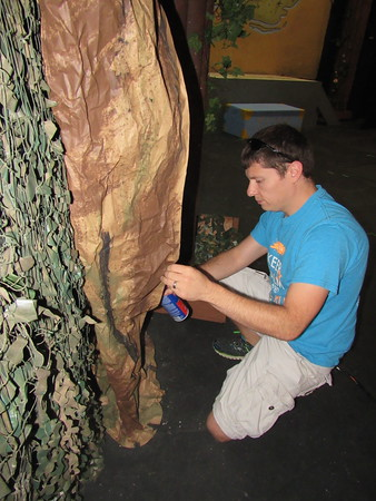 """Staff photo by Cathy Spaulding<br /> Sterling Spinks glues some paper """"bark"""" for a tree used in the Summer Youth Theatre production of """"Disney's Peter Pan Jr."""""""
