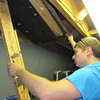 """Staff photo by Cathy Spaulding<br /> Sterling Spinks goes under the Muskogee Little Theatre stage to work on a trap door for the MLT Summer Youth Theatre production, """"Disney's Peter Pan Jr."""" Spinks majored in theater at Northeastern State University."""